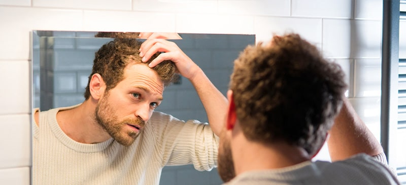 Mann entdeckt erste Anzeichen von Geheimratsecken im Spiegel