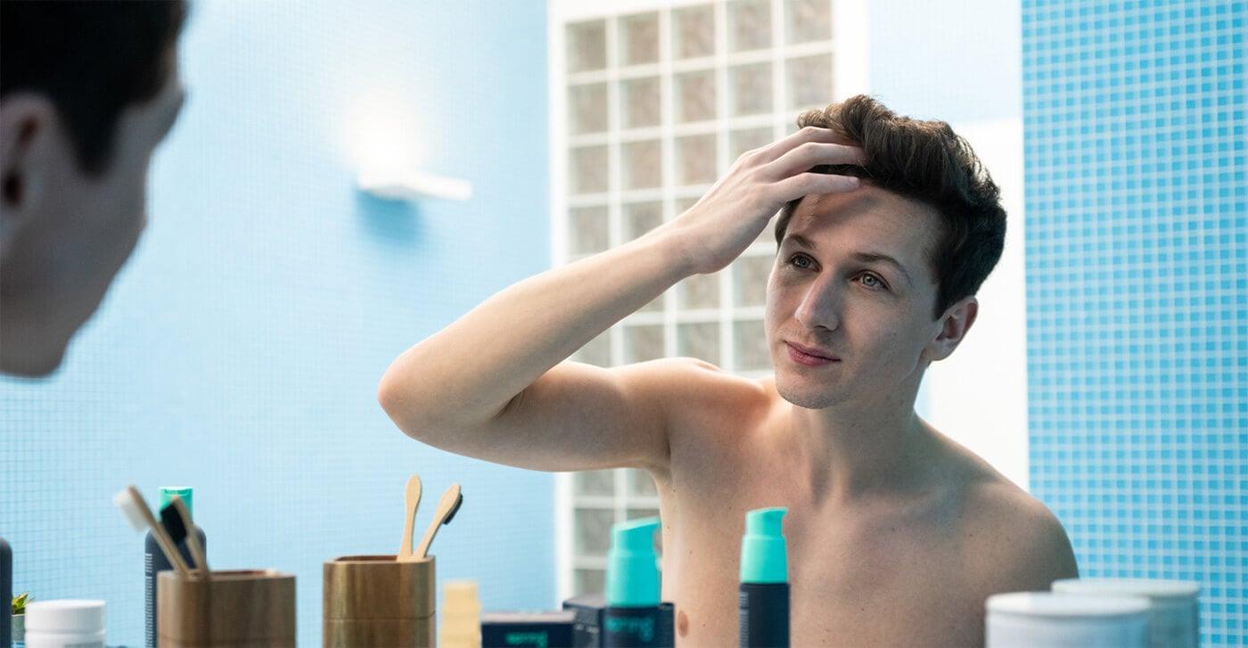 Junger Mann entdeckt erste Anzeichen von Haarausfall im Spiegel