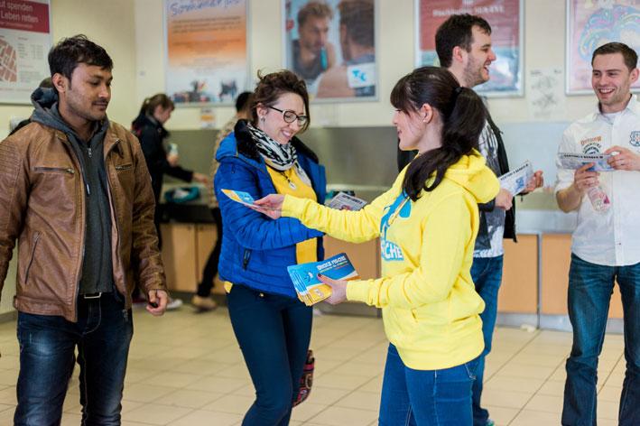Eine studentische Mitarbeiterin überreicht einem Studenten ein Dicke Fische Gutscheinheft