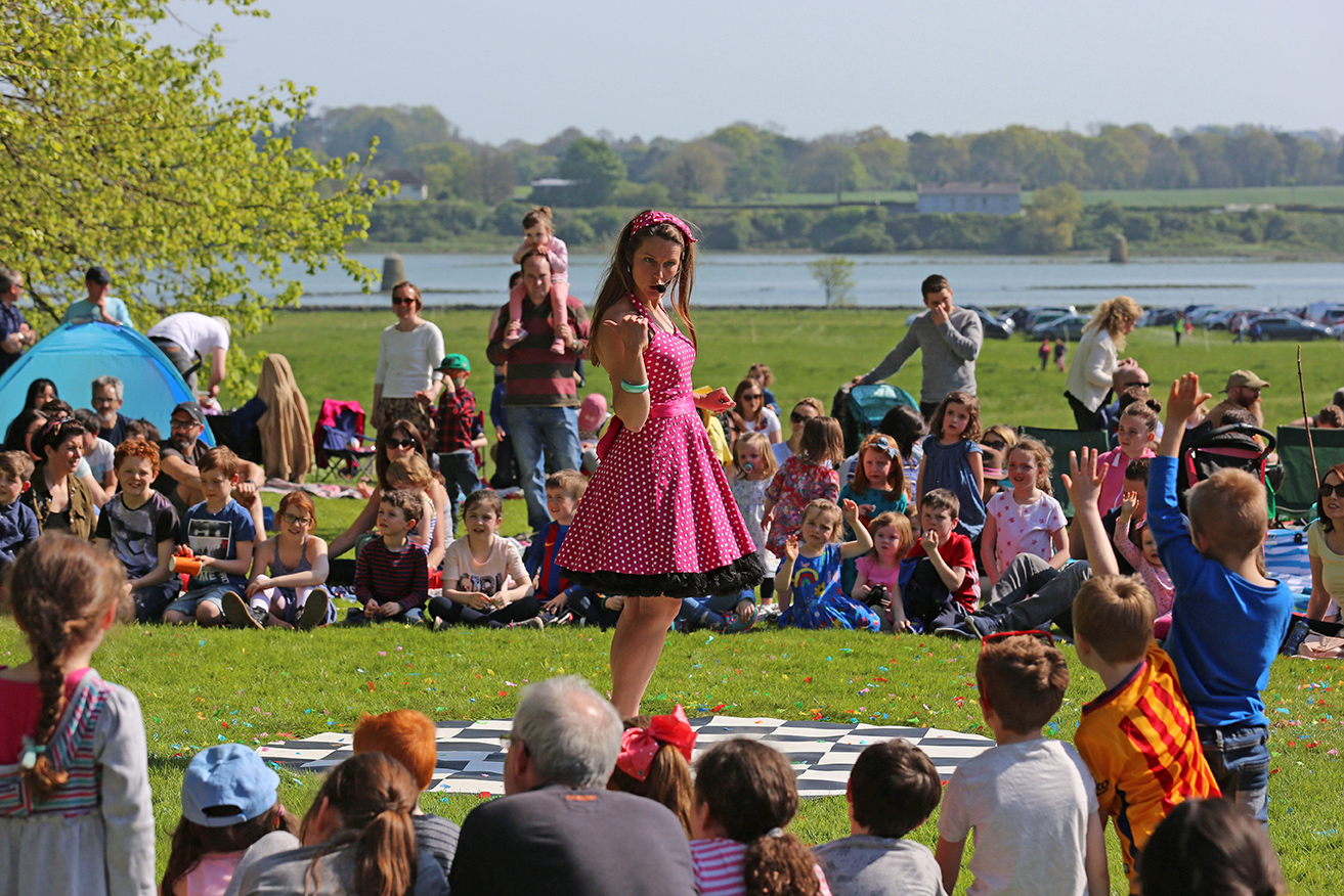 Event Photography by Jenny Matthews Photography, girl in a pink dress entertains children at Drogheda Arts Festival, Beaulieu House and Gardens