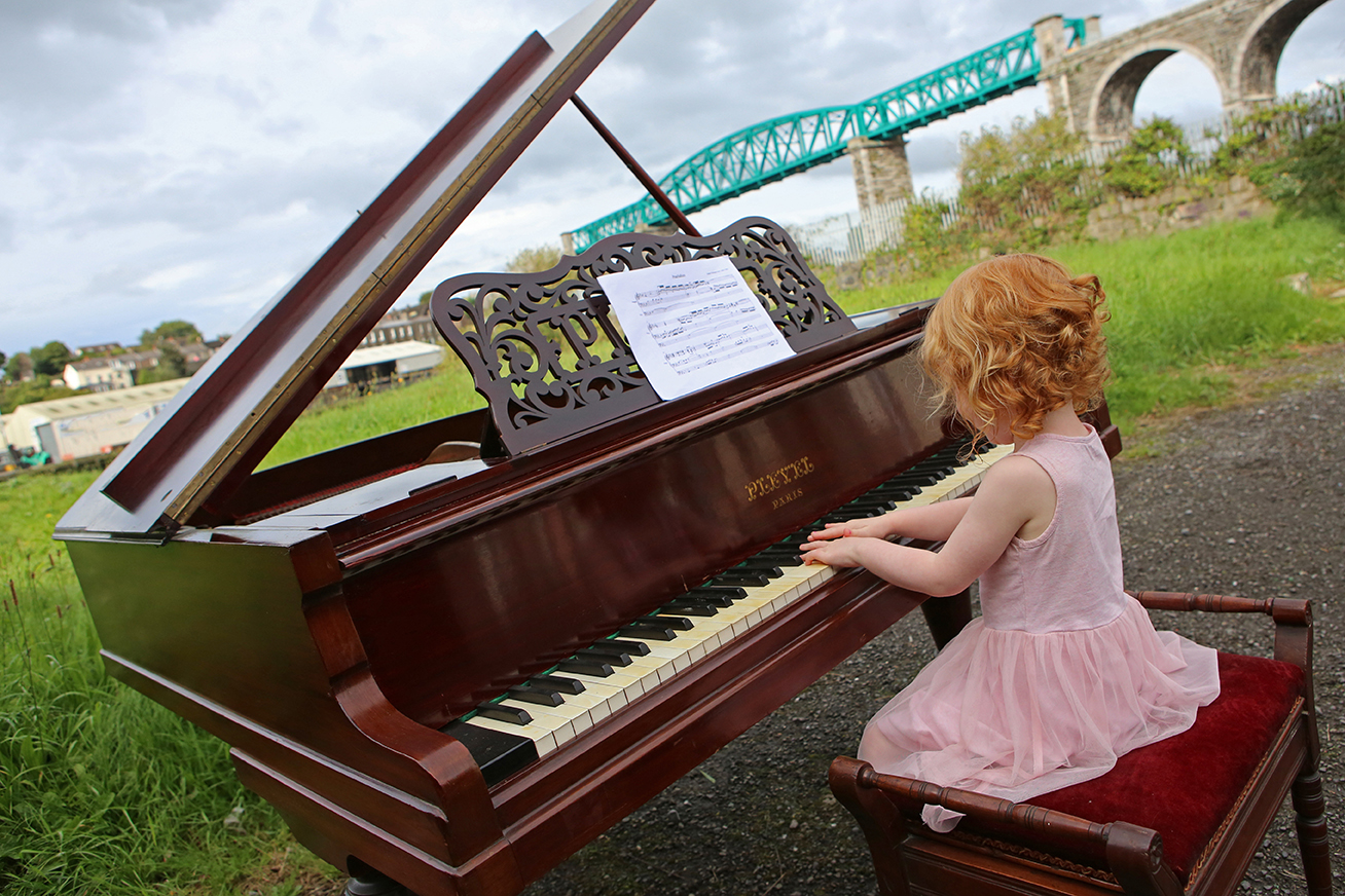Event Photography by Jenny Matthews Photography, young girl in pink dress plays piano with viaduct in the background, Drogheda Classical Music Series