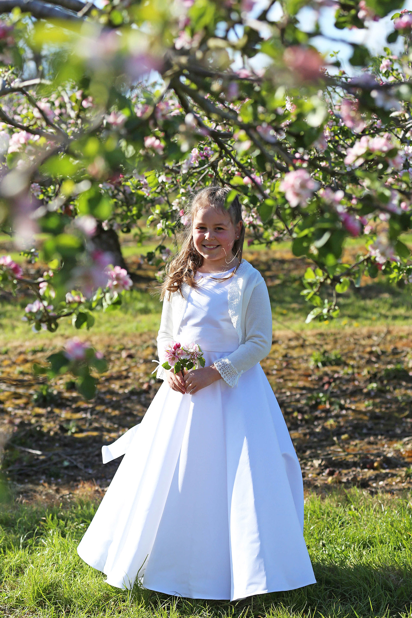 Communion girl with apple blossom trees by Jenny Callanan Photography