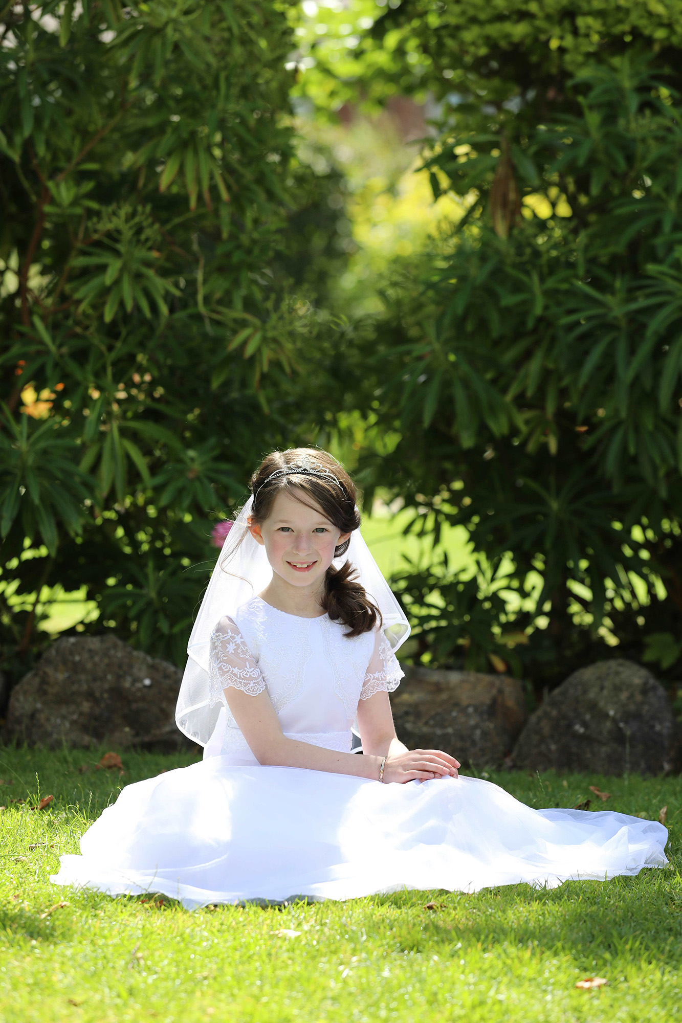 Communion girl sitting on the grass by Jenny Callanan Photography