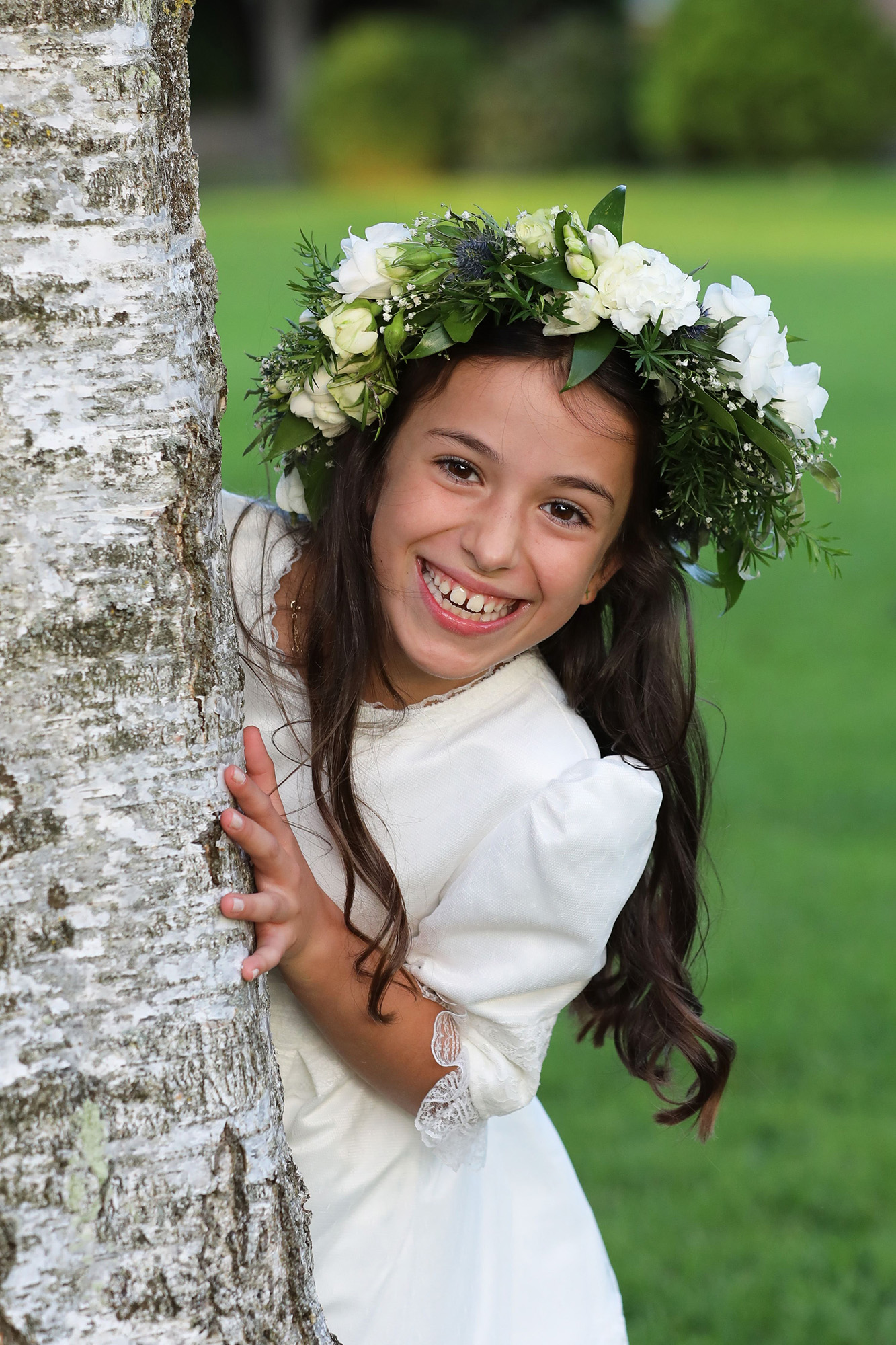 Communion girl peeping around tree by Jenny Callanan Photography