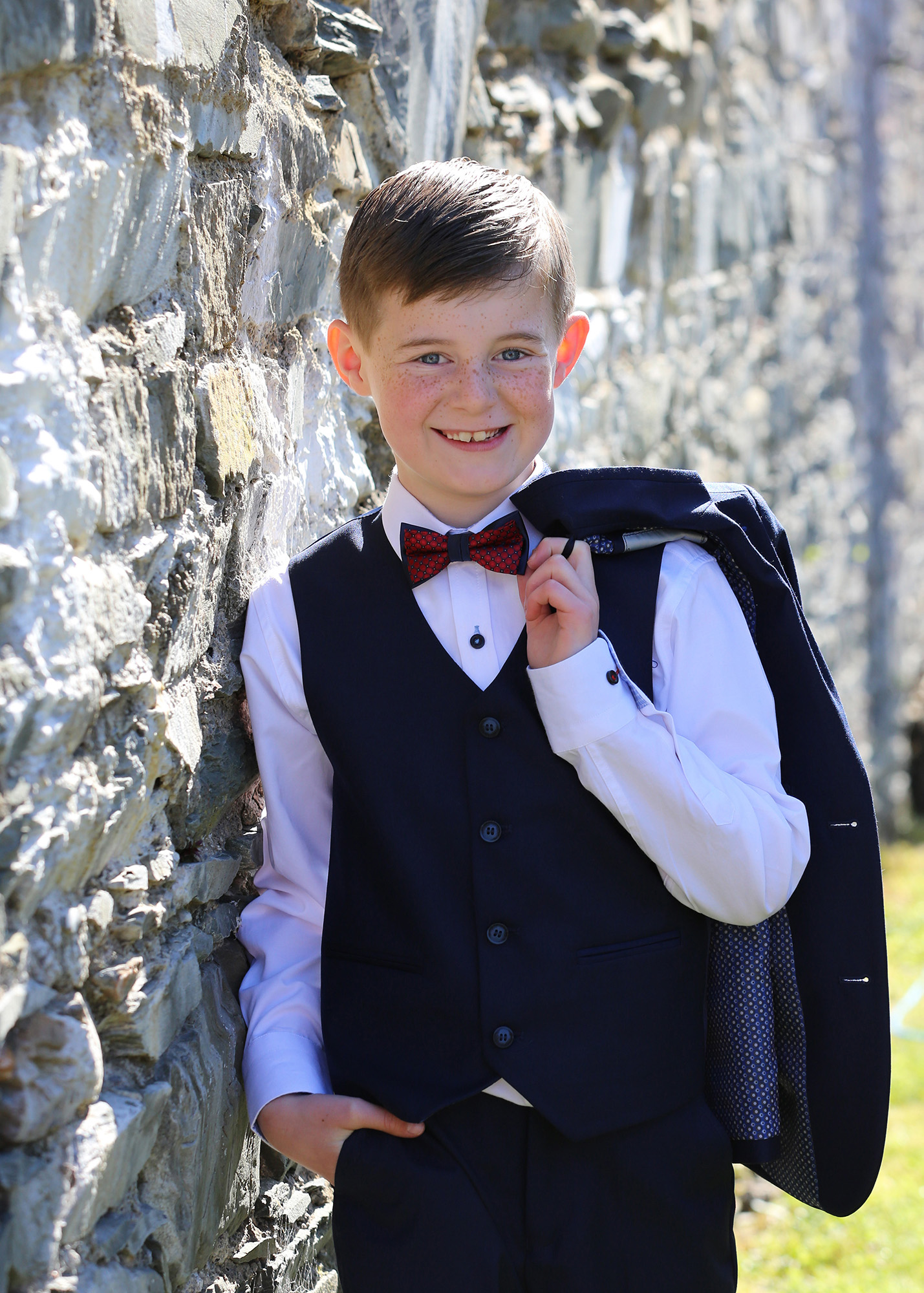 Communion boy leaning on a wall by Jenny Callanan Photography