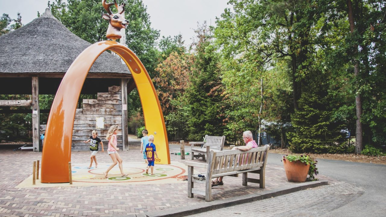 children playing under adult supervision under the yalp sona arch interactive play equipment
