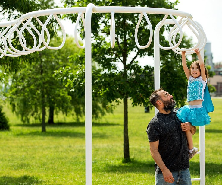 Father at a playground helping his daughter to play on the monkey bars outside