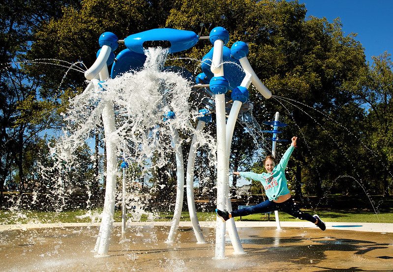 child jumping in front of water splash pad equipment spewing water
