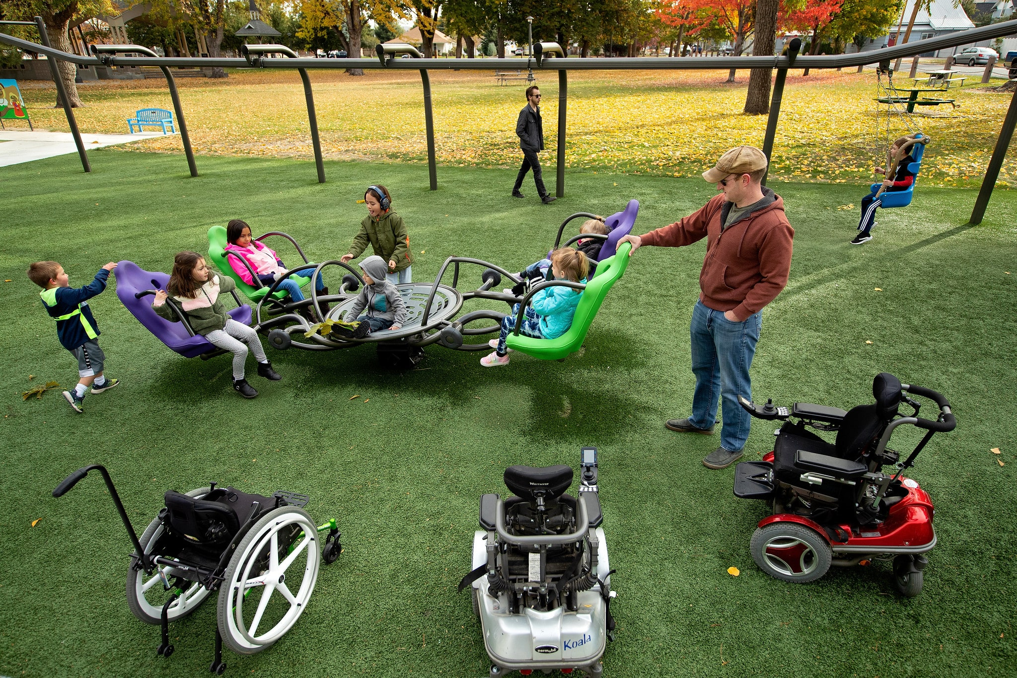 Group of children playing at an outdoor inclusive play ground/park.
