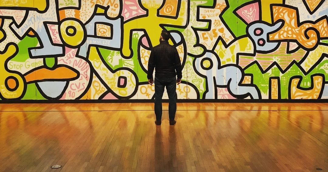 Man standing with his back facing us in front of a colorful wall