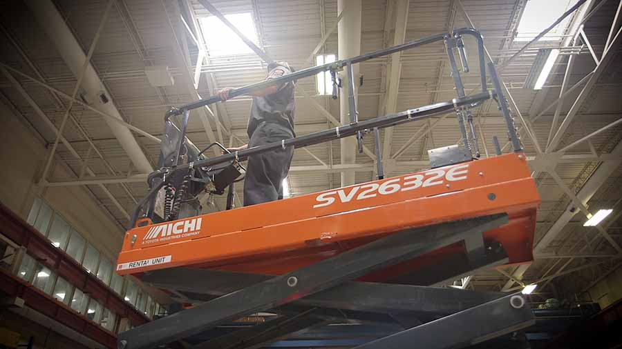 A technician being elevated in a scissor lift.