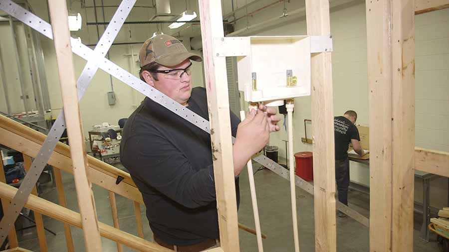 A young plumbing student working in a demo house at school.