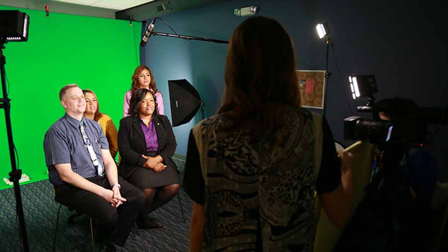Several people being interviewed in a green screen studio.