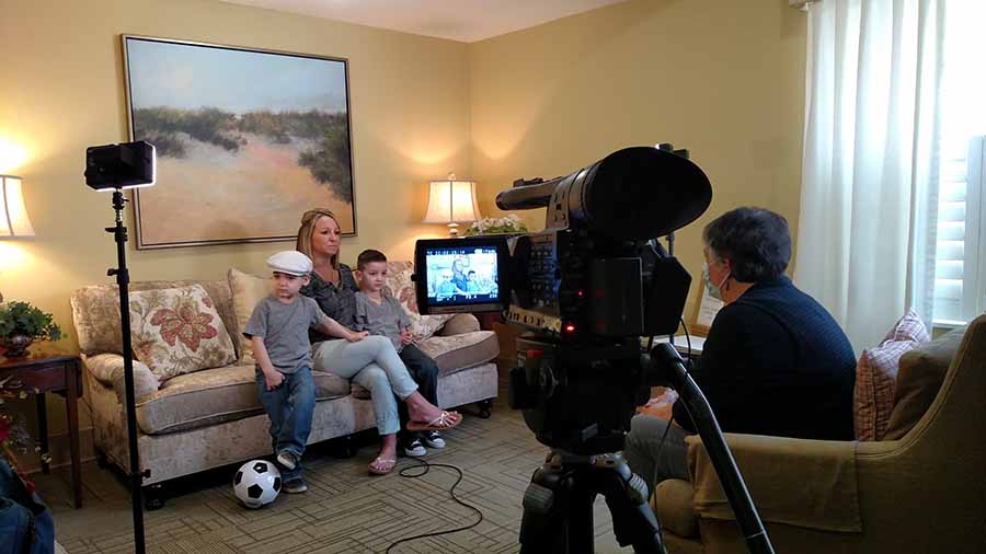 A mother and her two sons being interviewed at a Ronald McDonald House.