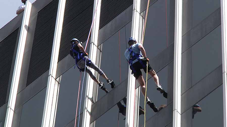 Two people rappelling down the side of a building in downtown Raleigh, North Carolina.