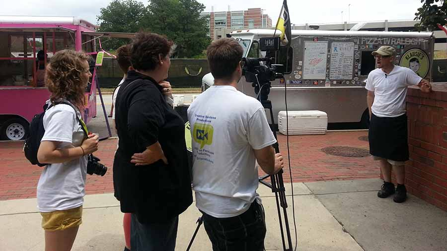 A food truck owner being interviewed in front of his truck in Raleigh, North Carolina