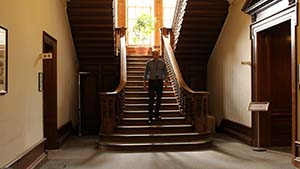 A man walking down an antique staircase in Hursley House.