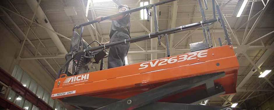A service technician testing a scissor lift.