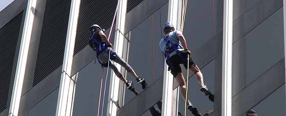 People rappelling down the side of a bank in downtown Raleigh, North Carolina during a fund raising event.