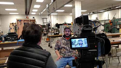 A young man being interviewed at a college lab.