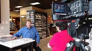 A man being interviewed in a tile store.