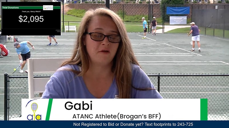 A young girl giving an interview with people playing tennis in the background.