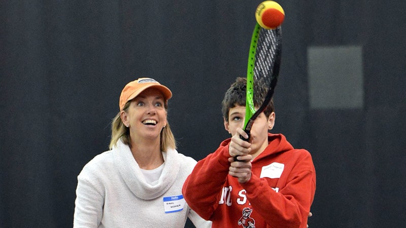 A young tennis athlete hitting a tennis ball while her coach looks on.