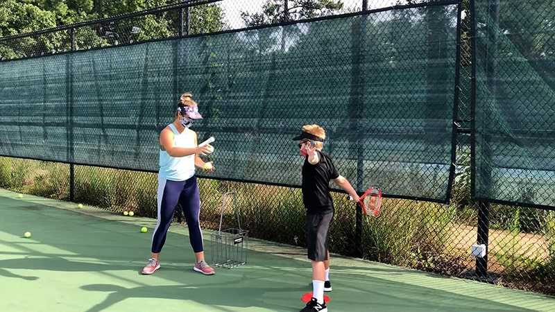 A young boy hitting tennis balls being tossed by his instructor.