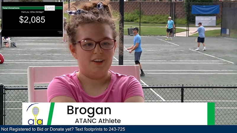 A young girl being interviewed with people play tennis in the background.
