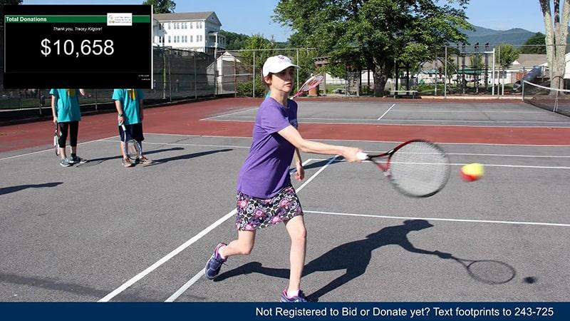 A young girl hitting a tennis ball.