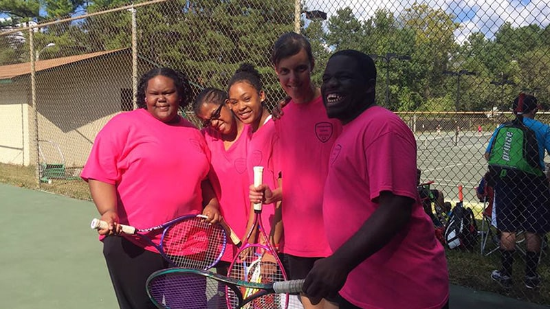 A group of people laughing and posing at a tennis court.