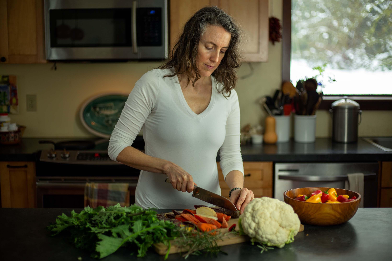 Annie Barrett chops vegetables in her kitchen