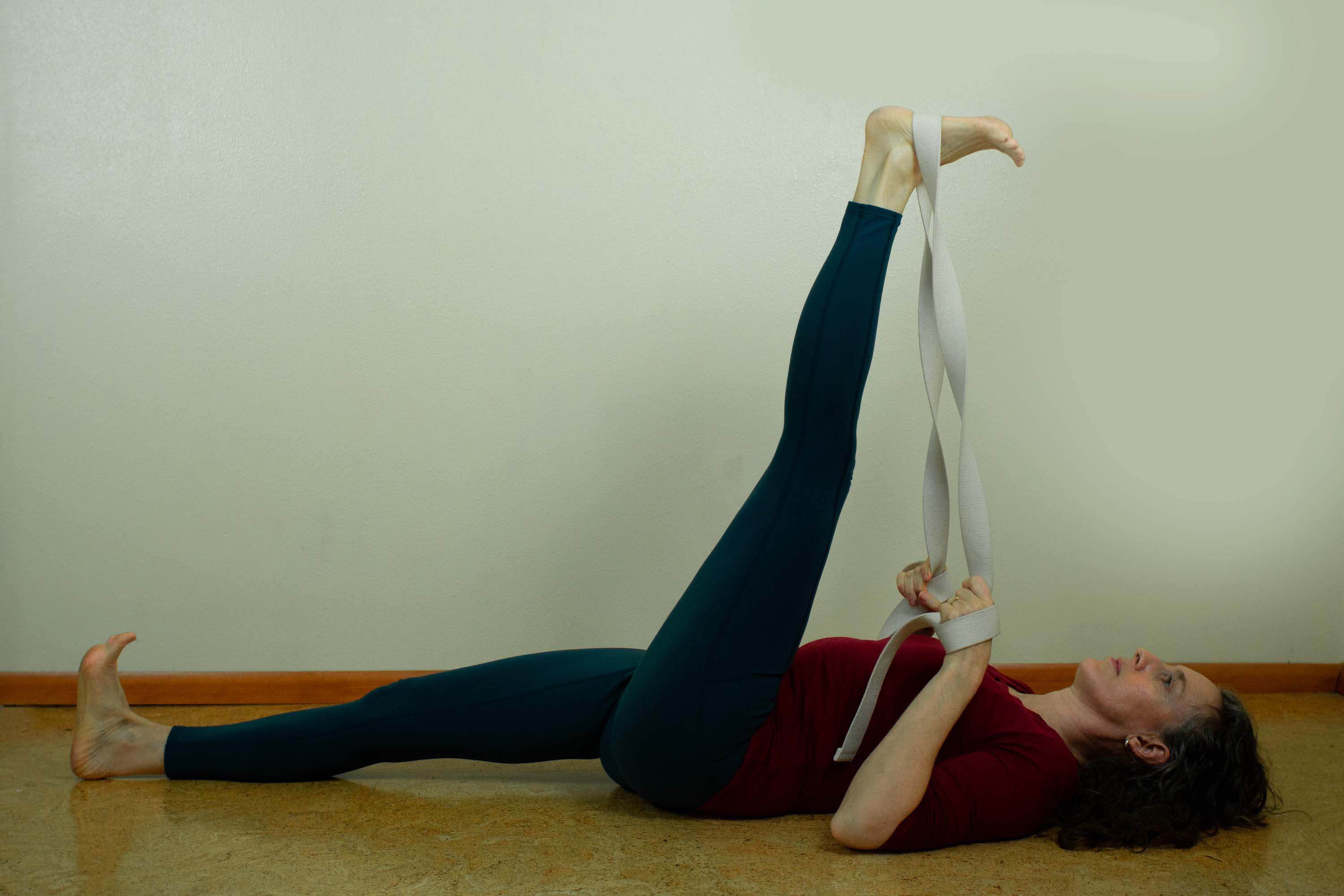 Annie Barrett doing a yoga pose lying on her back with her left leg held up in the air with the help of a exercise band.