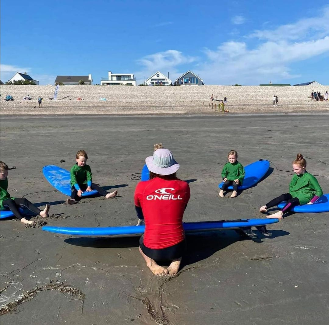 instructor teaching kids surf lessons on beach