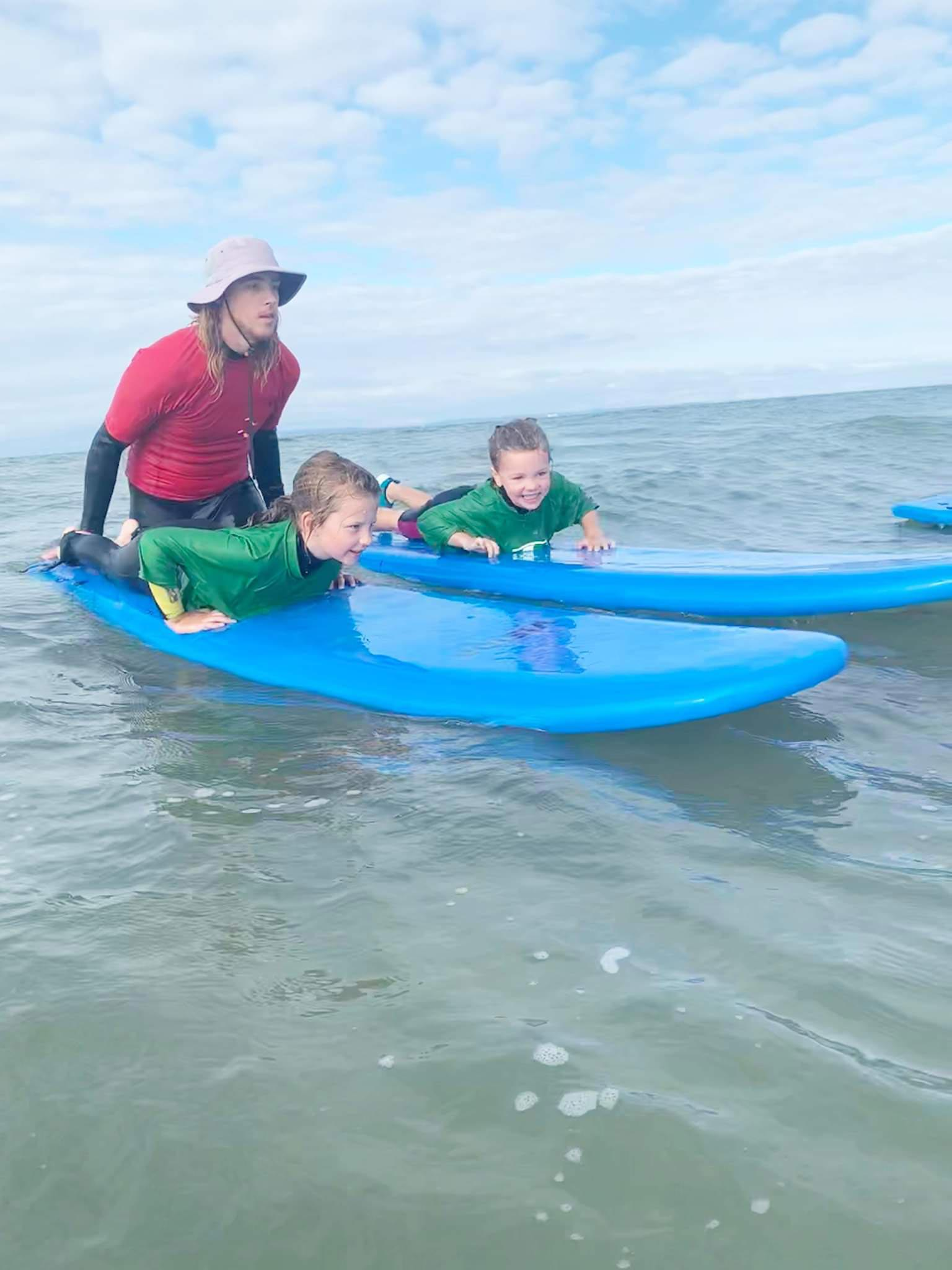 instructor teaching kids surf lessons