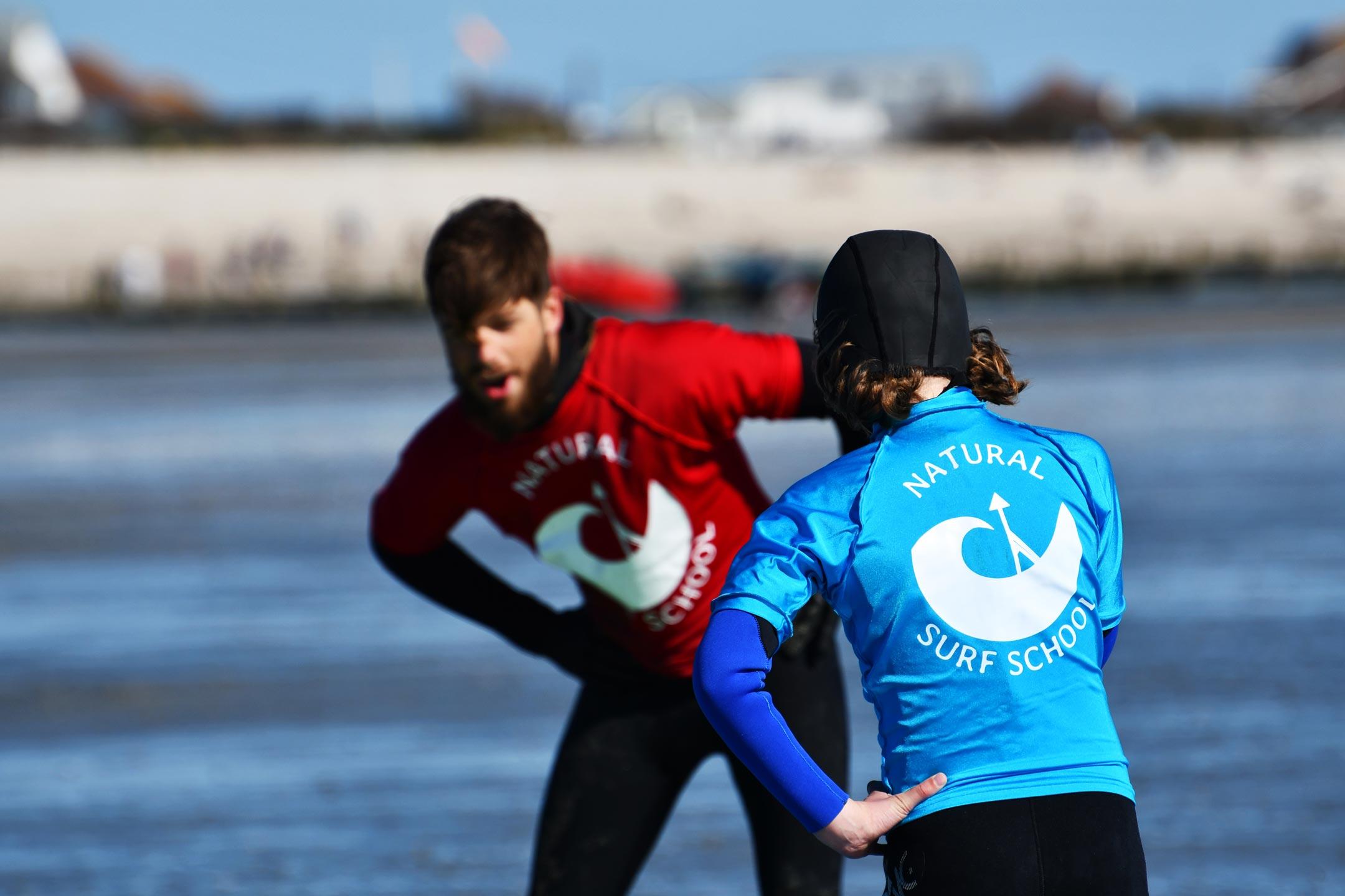 surf instructor teaching kids surf lesson