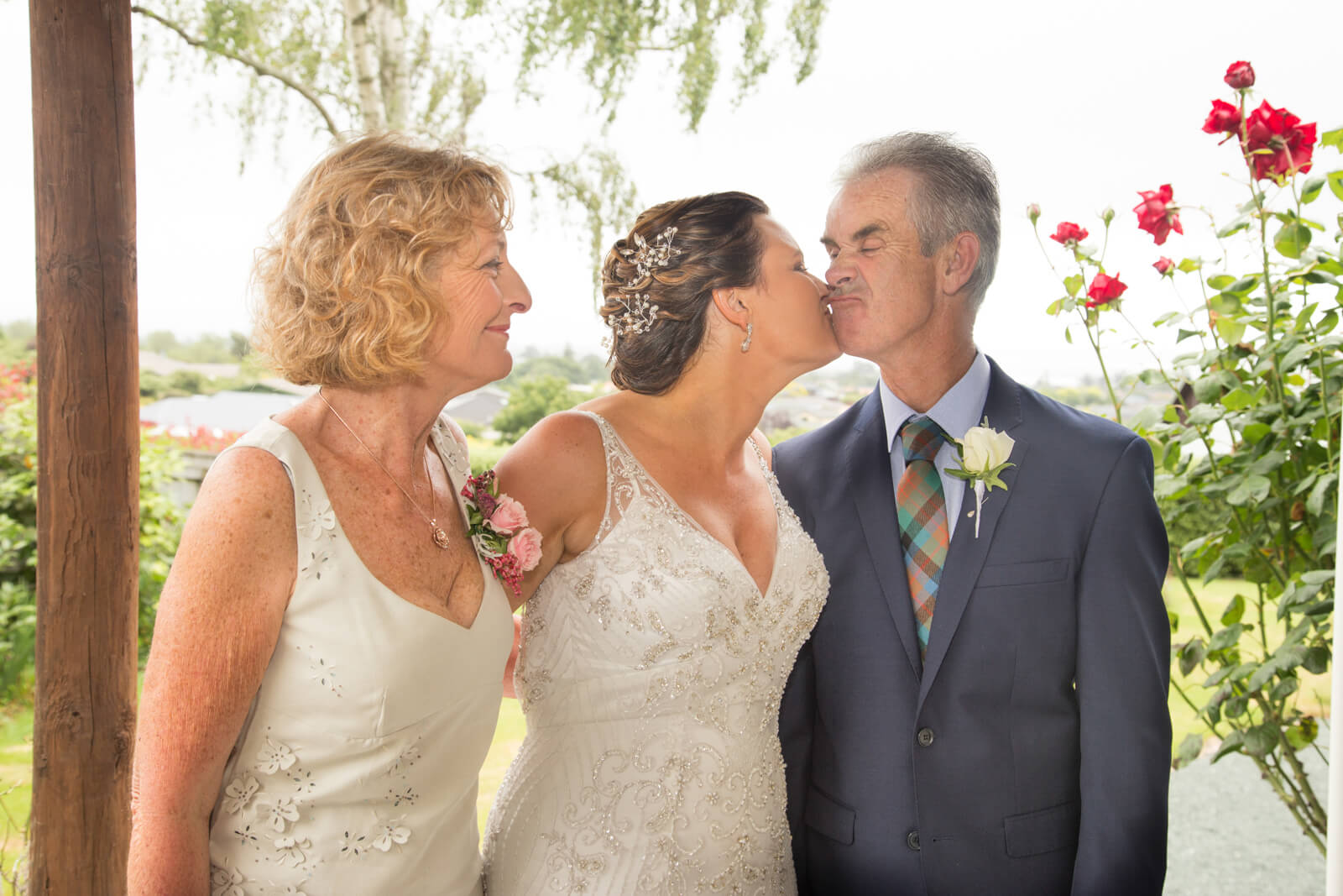 bride and groom kissing during a wedding watched by the bridesmaid