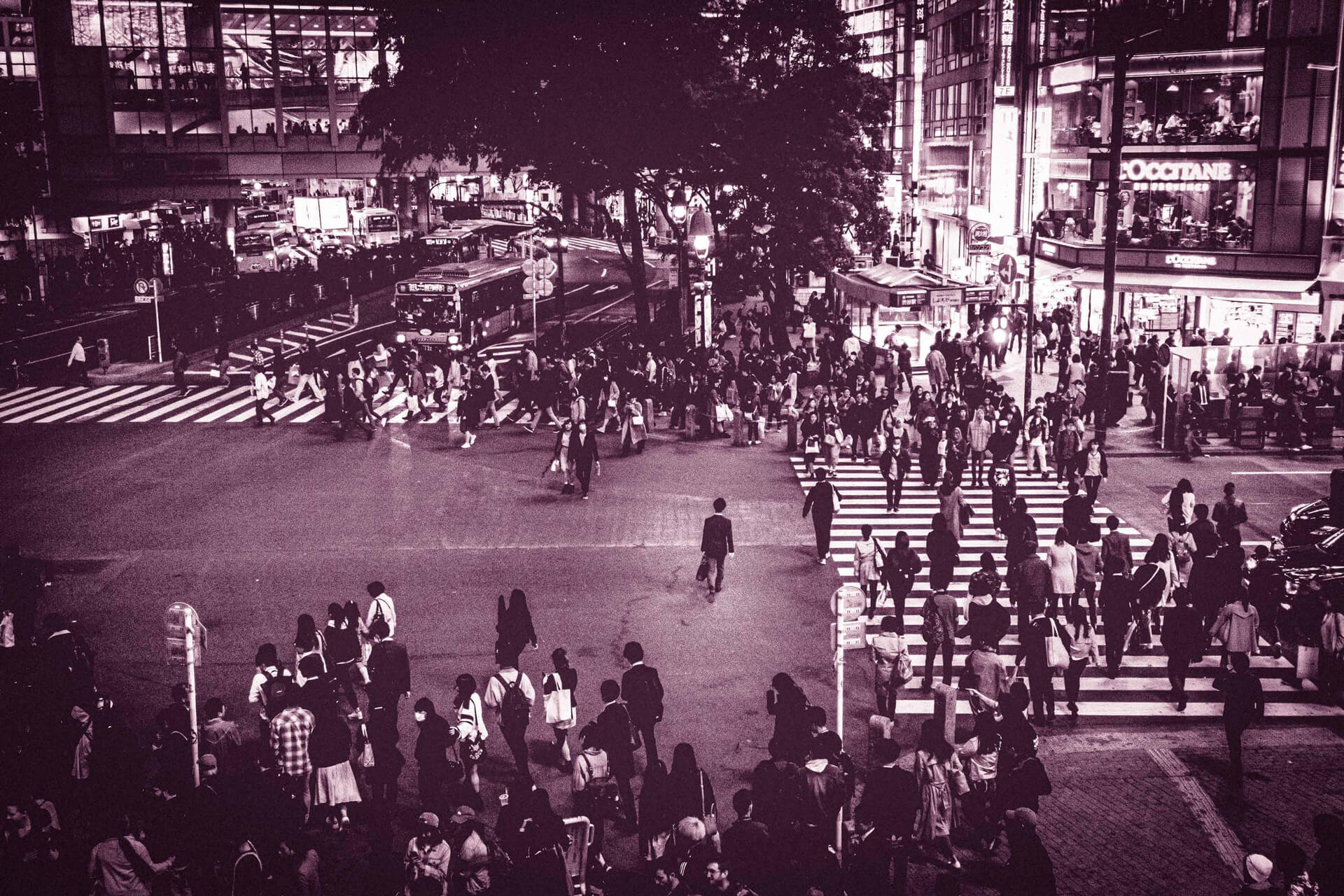 A crowded street with people walking.,