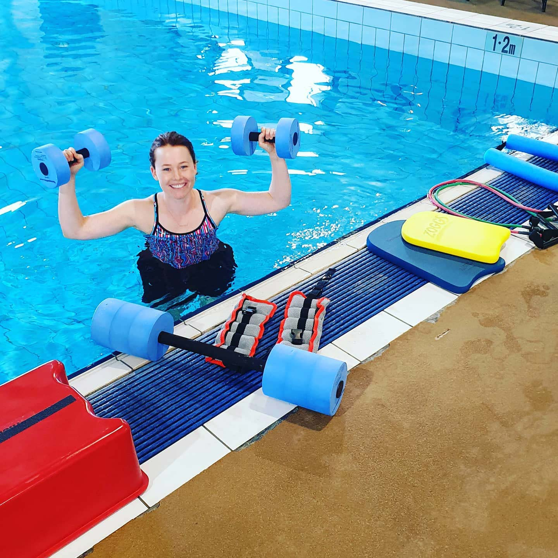 Ann Buchan in swimming pool carrying dumbells