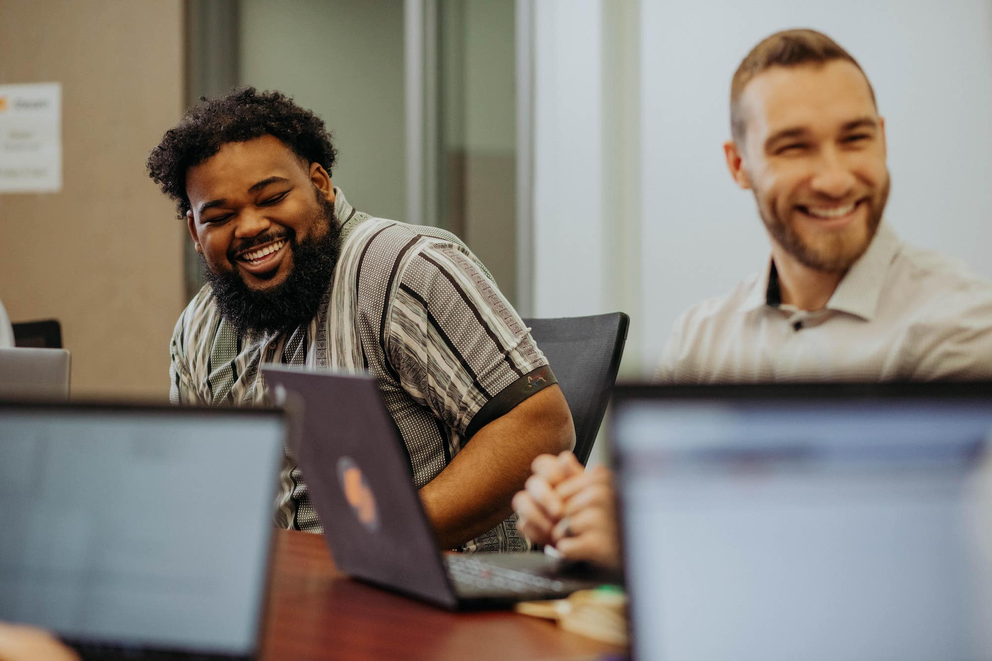 Two Steam Logistics Employees laugh while seated at the conference table.