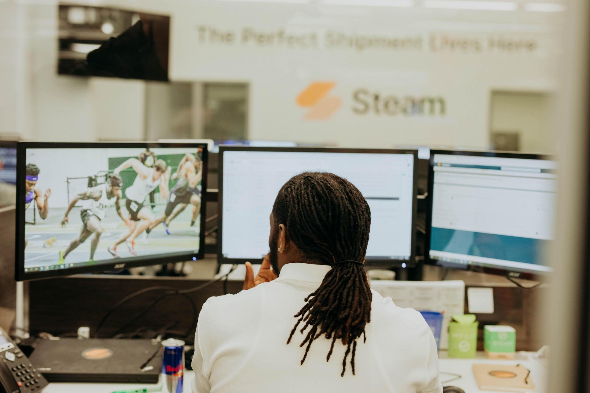 A Steam Logistics employee monitors three screens at his work station.