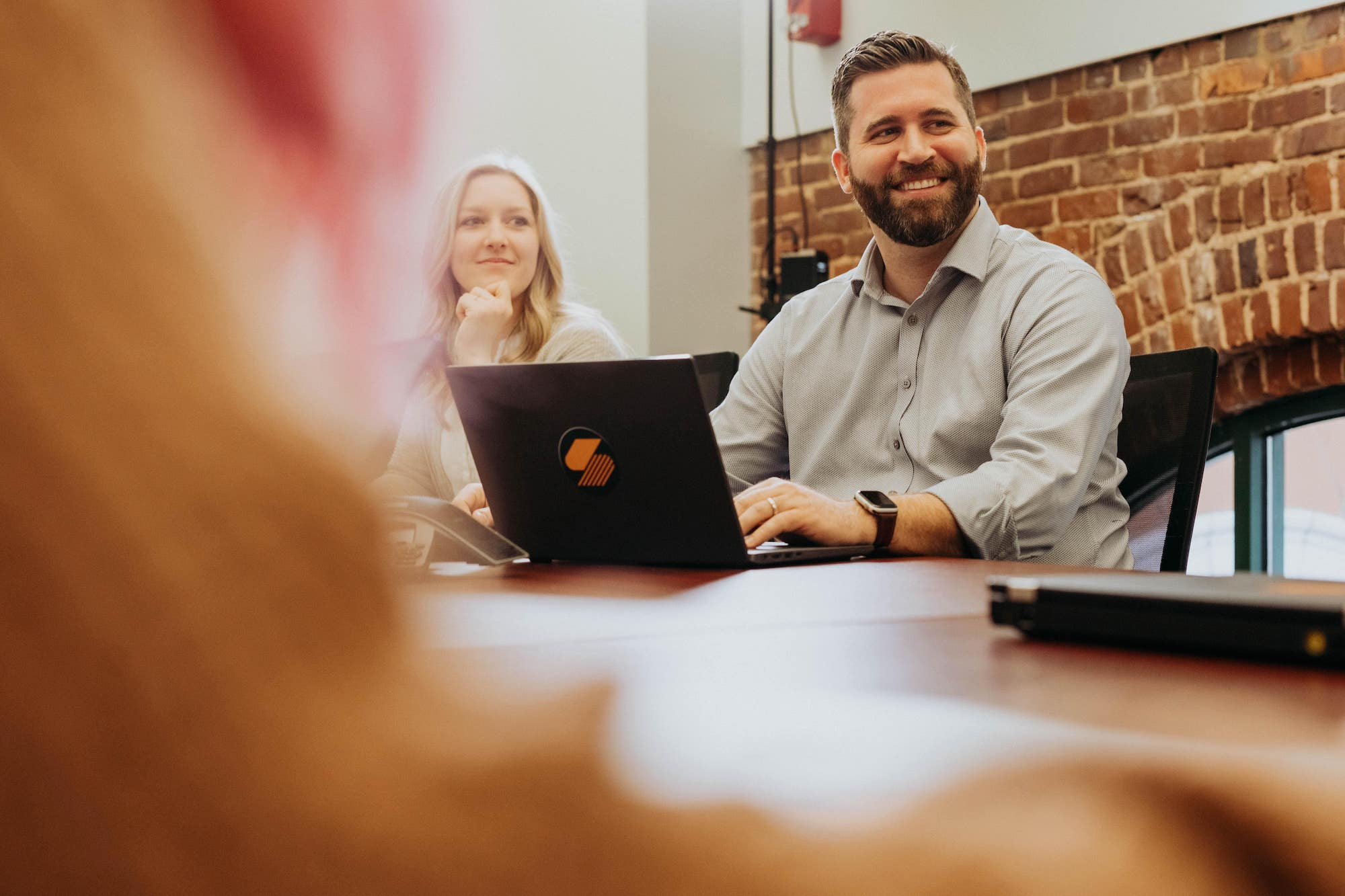 A Steam Logistics employee smiles while seated in the conference room, his laptop in front of him.