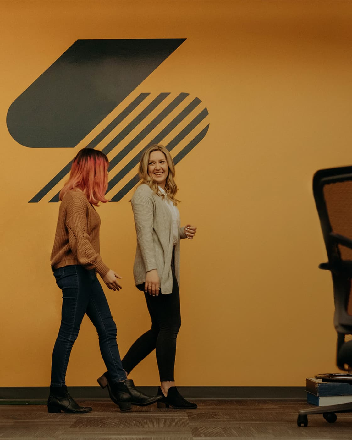 Two Steam Logistics employees walk through the bull pen, with the Steam logo displayed on the wall behind them.