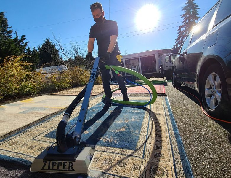 A area rug cleaning outside of the house.