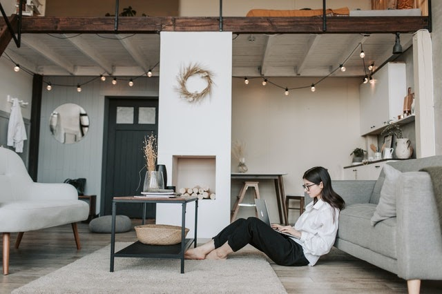 woman siting on floor with a laptop in living room
