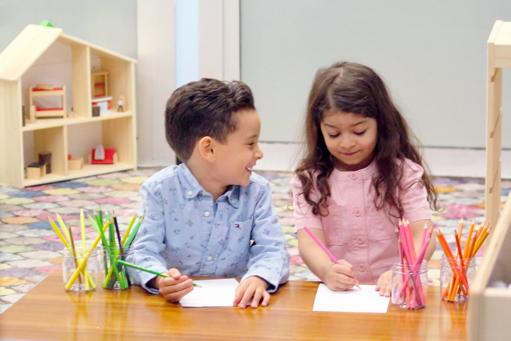 two children at a desk with pencils and paper