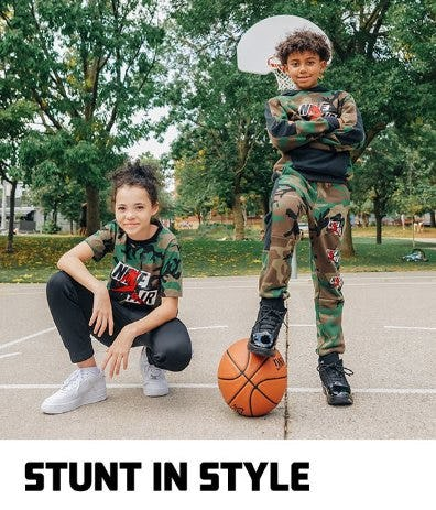 Young girl and boy in camo Nike clothes with a basketball