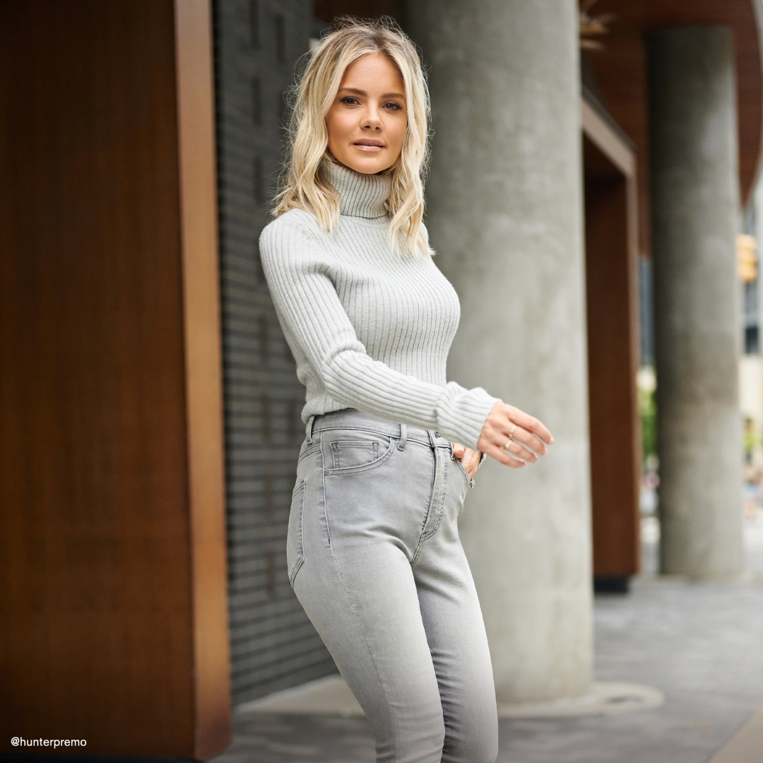 express model wearing light wash jeans and light grey turtleneck.