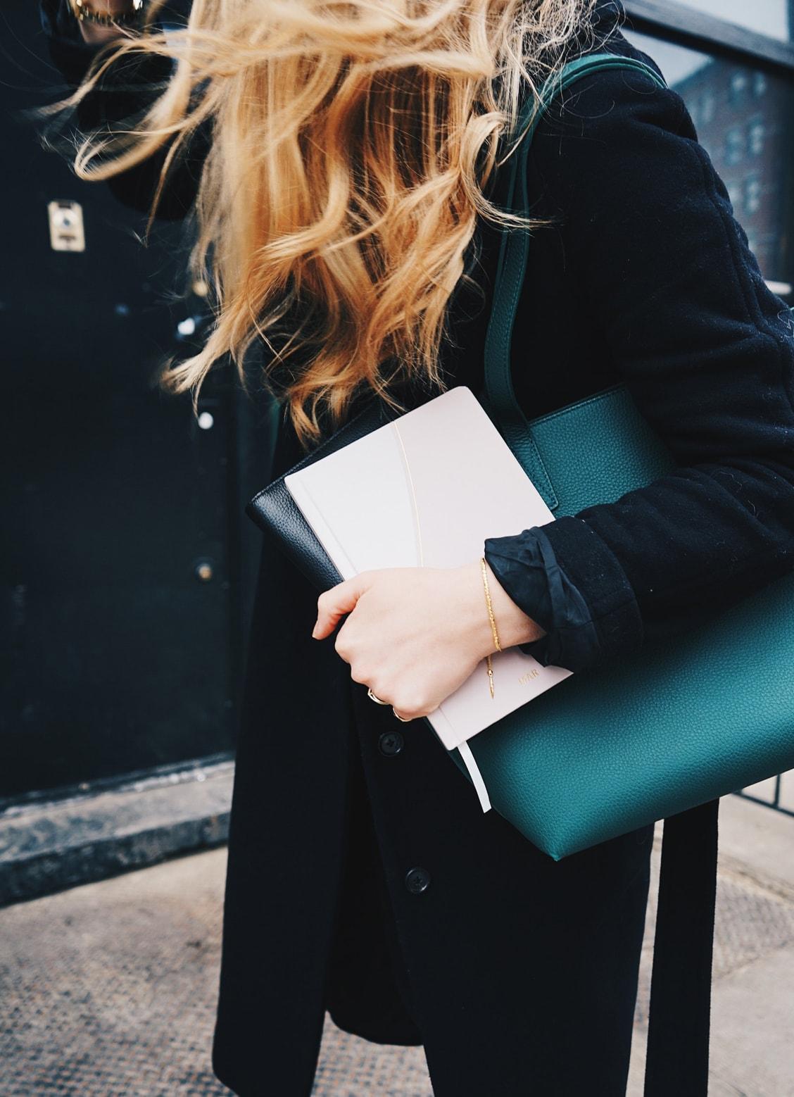 Kate holding books under arm