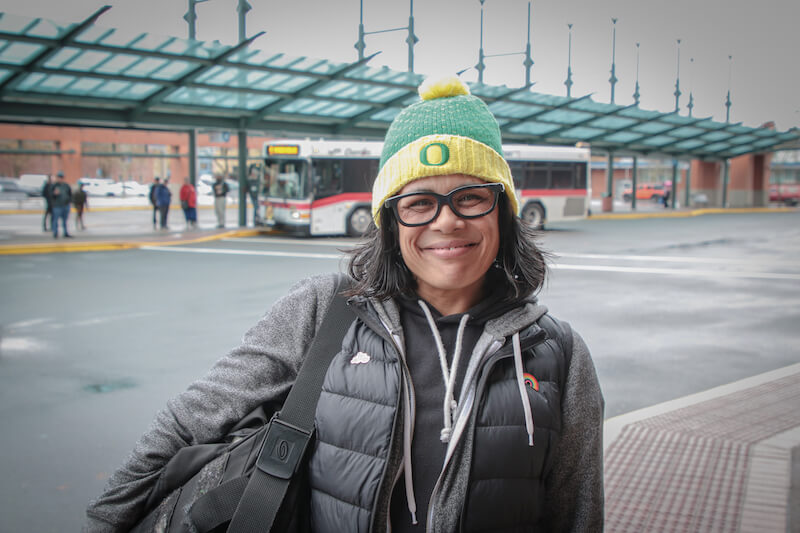 Person smiling in front of bus